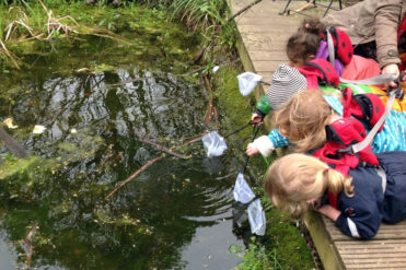children fishing in pond at Forest School