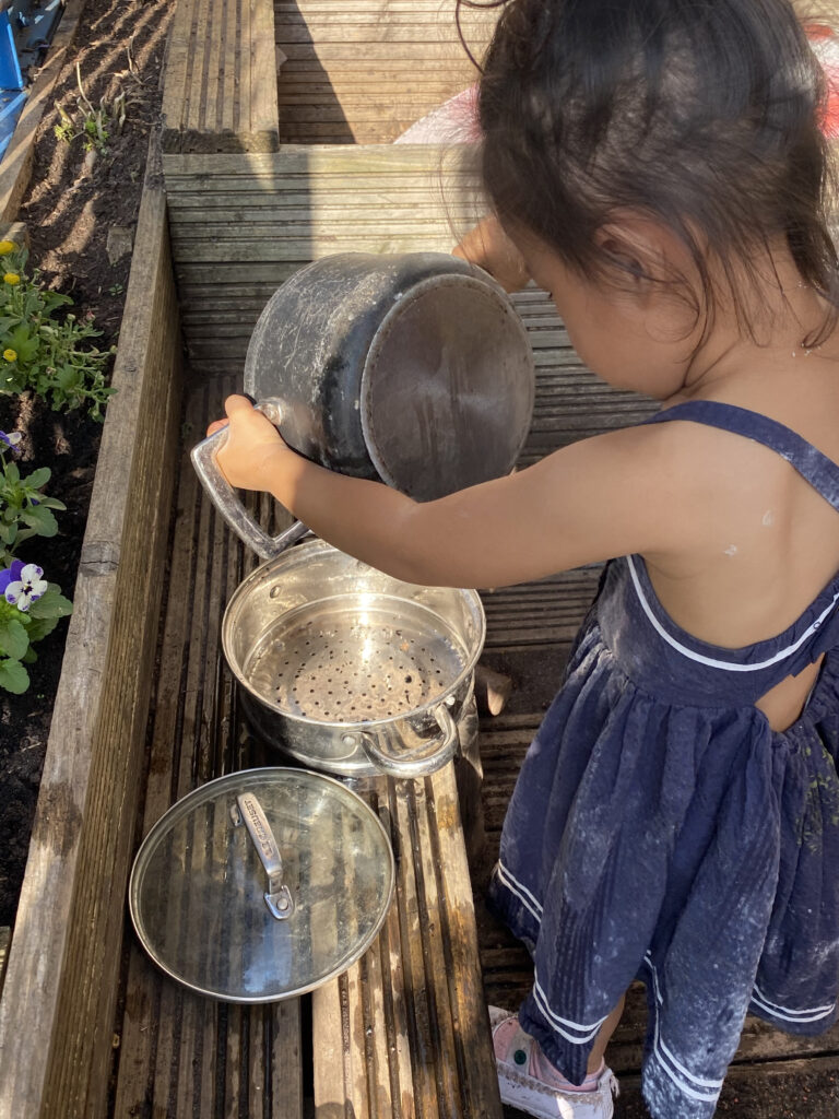Little girl outside poruing water into pots
