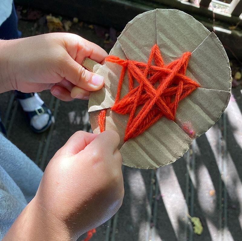 child's hand winding orange wool around cardboard pumpkin