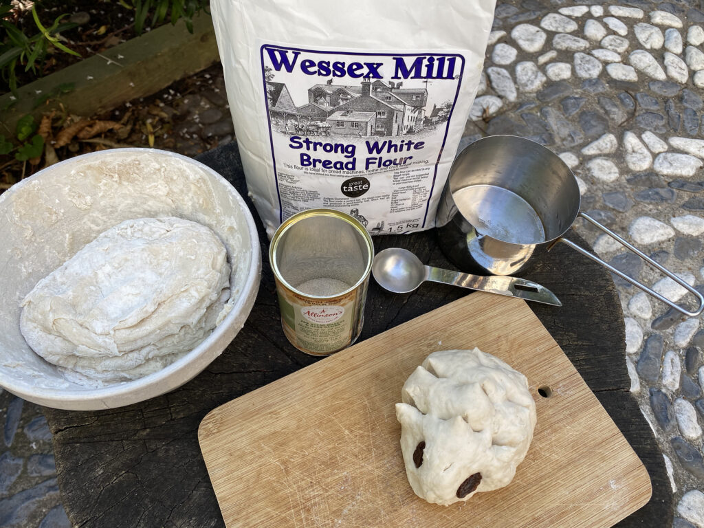 Breadmaking with bread dough, flour, yeast and measuring cup and spoon
