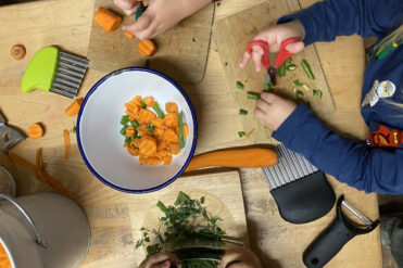 children at table chopping up vegetables